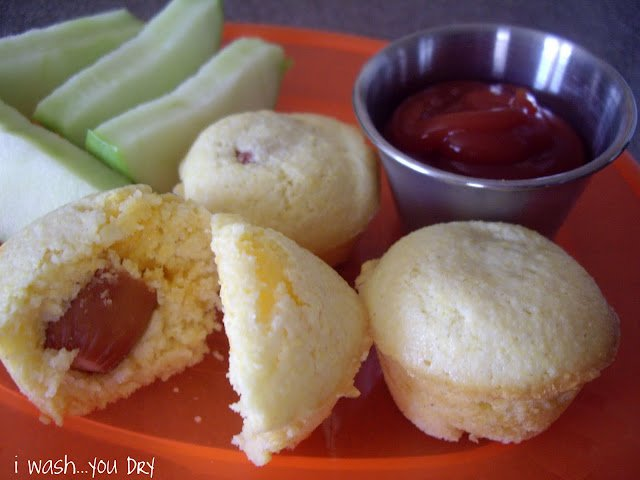 A plate displaying sliced apples, muffins and a side of ketchup.