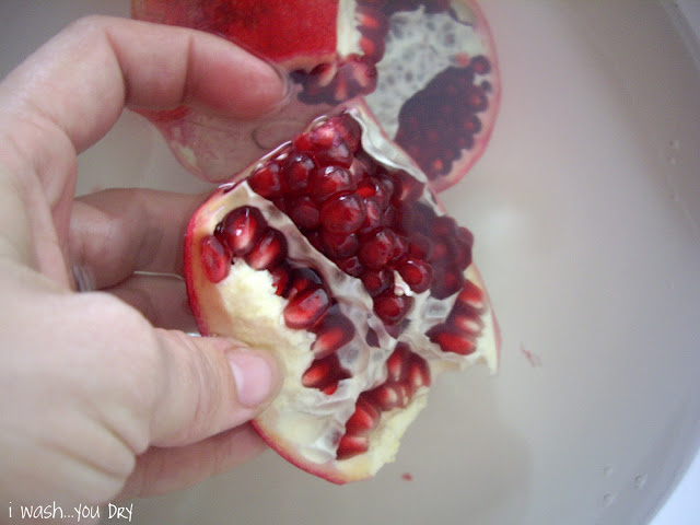 A hand showing the inside view of the newly removed slice of the pomegranate.