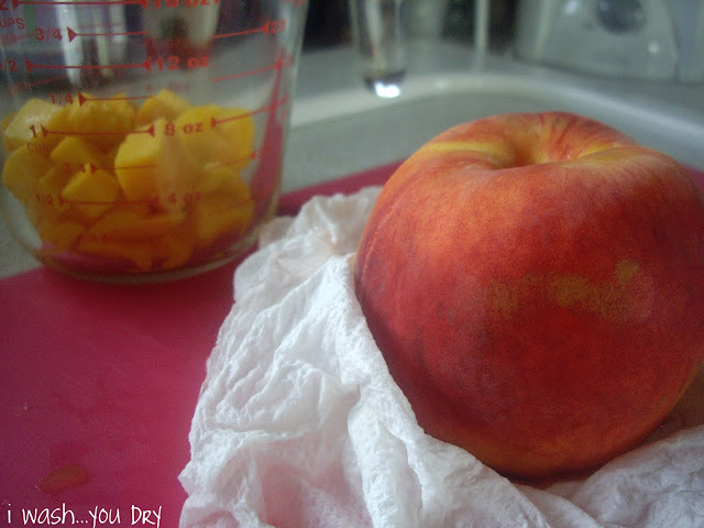 A peach on a cutting board with a glass measuring cup with cubbed mango pieces in it.