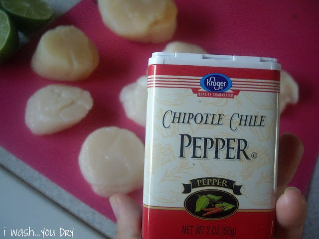 A hand holding a container of chipotle Chile pepper above sliced scallops on a cutting board.