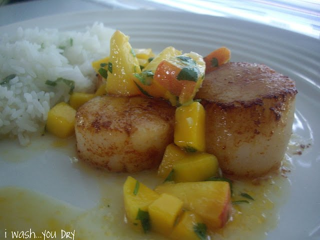 A plate displaying fried scallops topped with mango and peach salsa next to a side of rice.