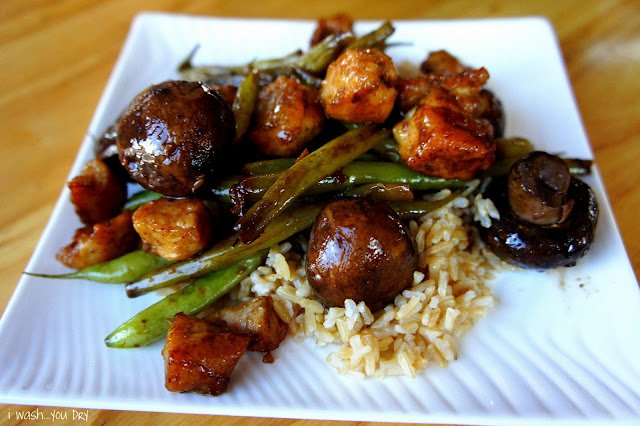 Mushrooms, chicke, green beans and rice displayed on a plate.