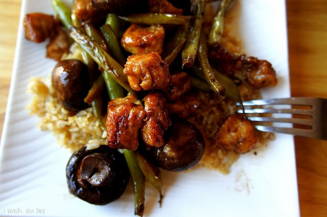 A close up of mushrooms, chicken, green beans and rice on a plate.
