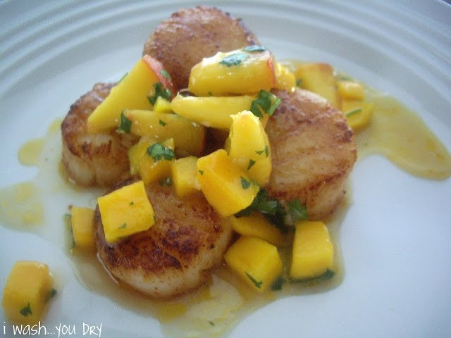 Scallops displayed on a plate topped with a mango and peach sauce.