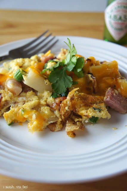 A plate of food on a table, with egg, ham and potatoes and cheese.