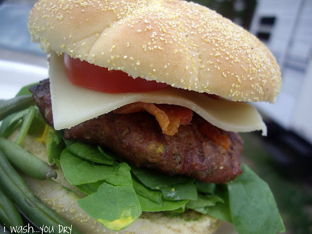 A close up of a burger, cheese, bacon, a tomato slice, and lettuce between two buns.