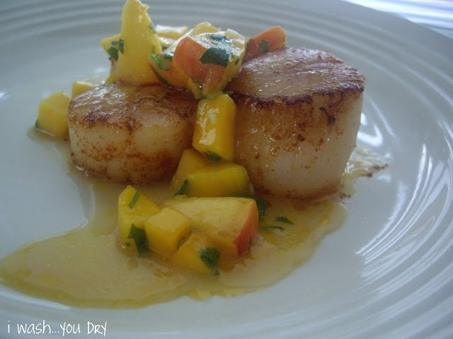 A close up of Scallops on a plate topped with a mango and peach sauce.