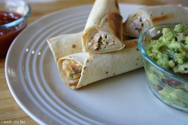 A close up of three flautas on a plate with one cut in half to display the inside.