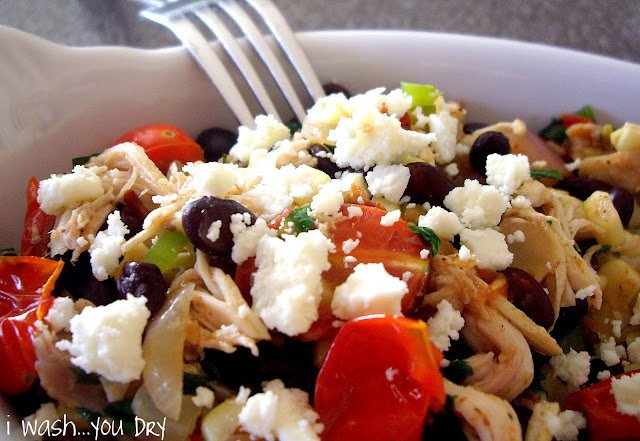 A dish filled with food, with shredded chicken, tomatoes, olives and cheese.