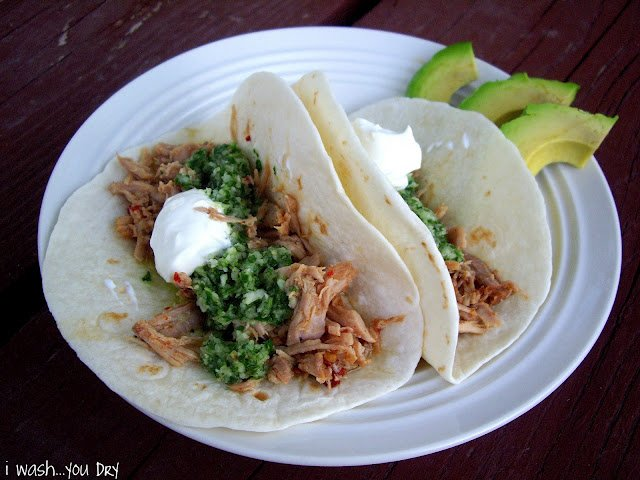 A display of two tacos on a plate with a side of avocado slices.