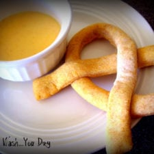 A homemade pretzel on a plate next to a small bowl of dipping sauce.