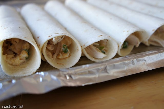 A close up of a baking pan with rolled flautas on it.