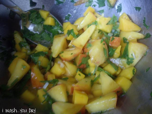 A spoon stirring a bowl with mango and peach salsa.