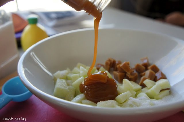 Liquid caramel topping being added on top of the chopped apples in a bowl.