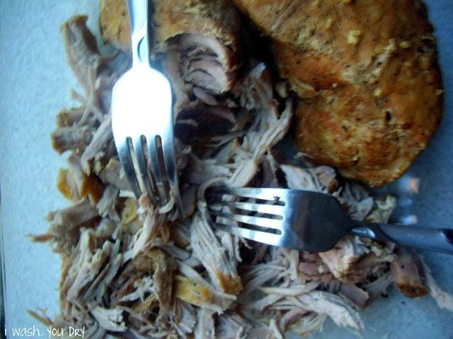 Two forks shredding pork on a cutting board.