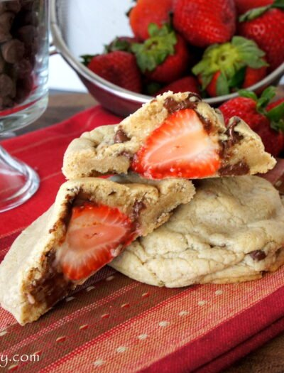 A close up look of a Strawberry stuffed Chocolate Chip Cinnamon Cookie split in half to showcase the stuffed strawberry