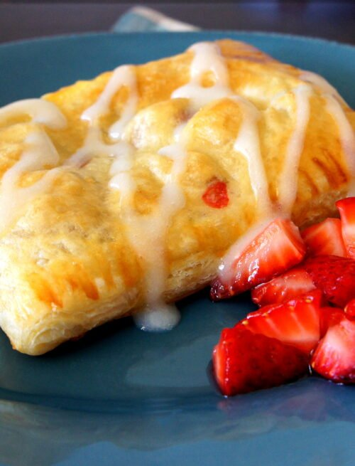 A close up of a Homemade Strawberry and Cream Cheese Toaster Strudel on a plate, with a side of diced strawberries