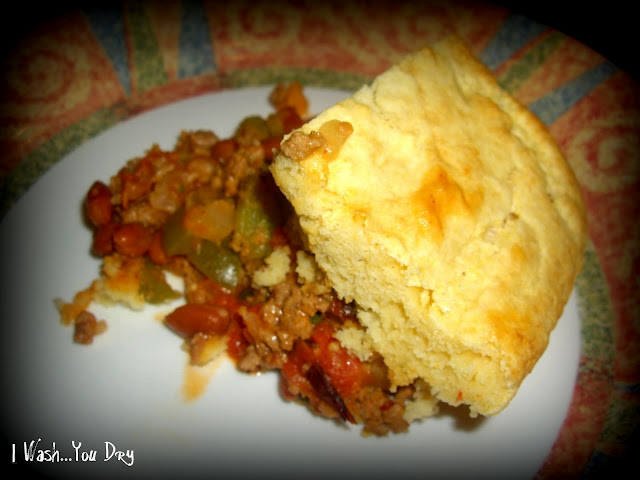 A plate of food: meat mixture topped with breading
