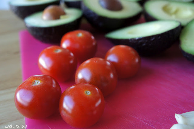 A close up of cherry tomatoes and avocado halves on a cutting board.