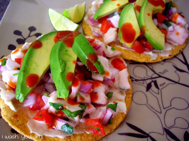 Slices of avocado on top of veggies and a small tortilla.