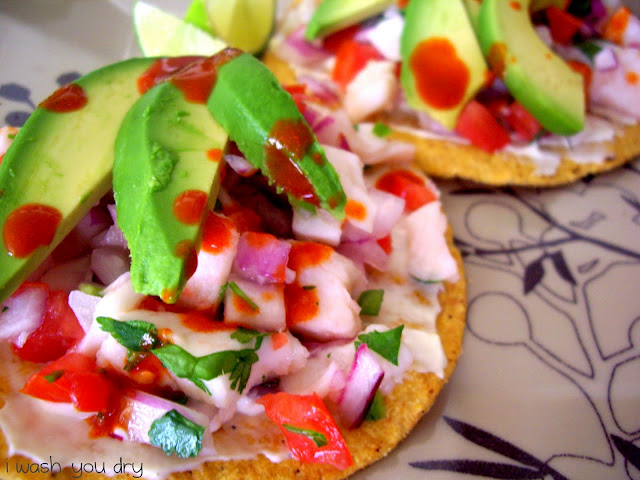 Slices of avocado on top meat and veggies on a tostada shell.
