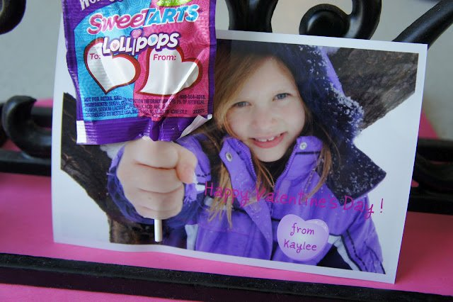 A close up of a Valentine\'s Day card; picture of little girl holding hand out with a lollipop attached to the picture.