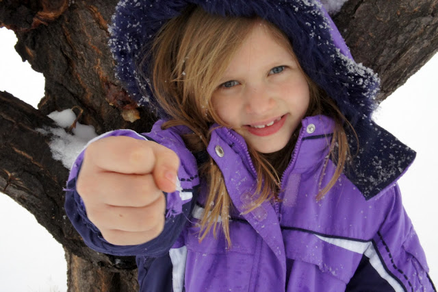 A little girl holding a fist out.