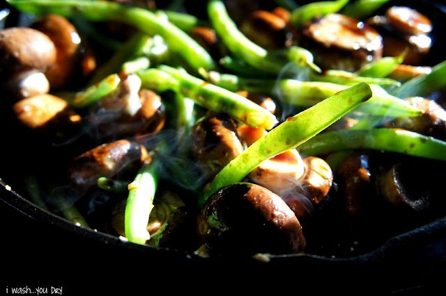 A close ups green beans, mushrooms and chicken in a skillet.
