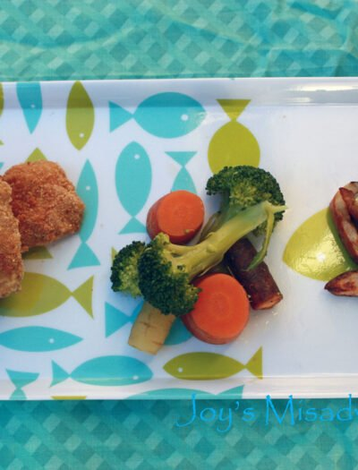 A plate of Cornbread Chicken Nuggets with a side of broccoli and carrots and potato fries