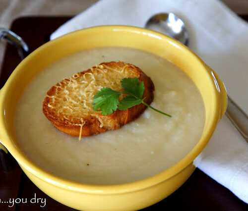 A bowl of Creamy Cauliflower Soup with a Asiago Crouton on top
