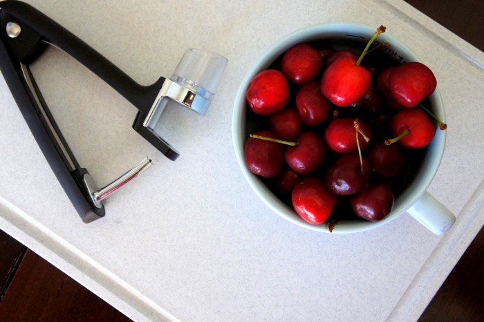 A close up of a bowl of cherries ready to be pitted