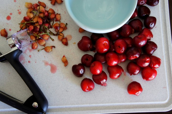 A close up of a cutting board with a pile of cherry seeds, a pile of cherries and an empty bowl