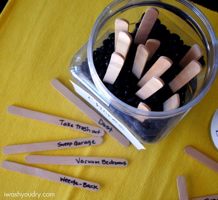 A look down on popsicle sticks with jobs on them next to a jar with stick poking out of it