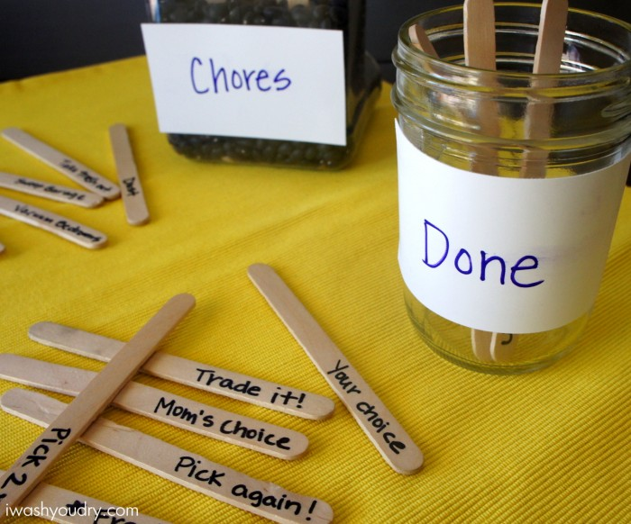 "Sticks with jobs on them infant of two jars on a table. One jar with the labeled ""Chores\"" and the other labeled \""Done\"""