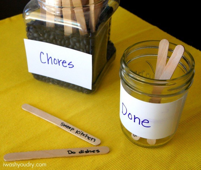 """Two jars on a table with sticks in it. One jar with the labeled \""""Chores\"""" and the other labeled \""""Done\"""""""
