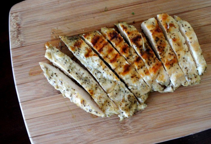 Slices of grilled chicken strips on a cutting board