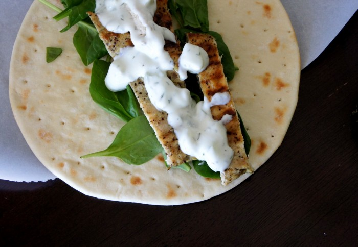 A close up of spinach, grilled chicken, sauce on a pita