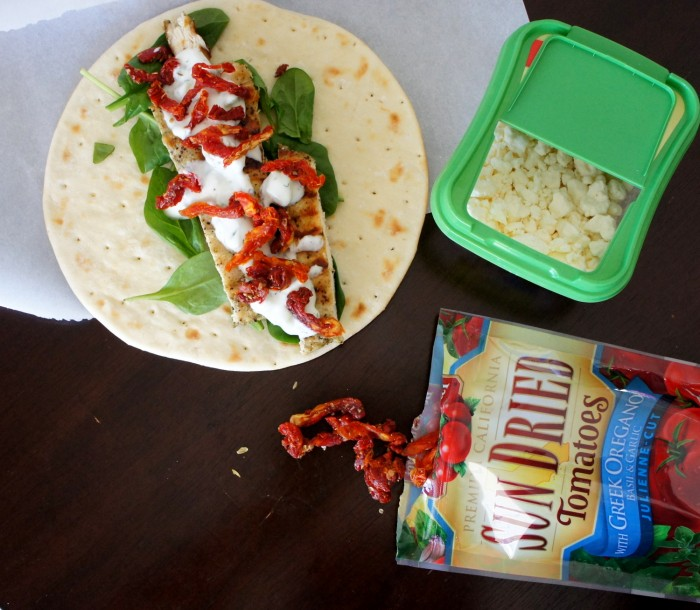 Spinach, grilled chicken, sauce, sun-dried tomatoes, cheese on a pita