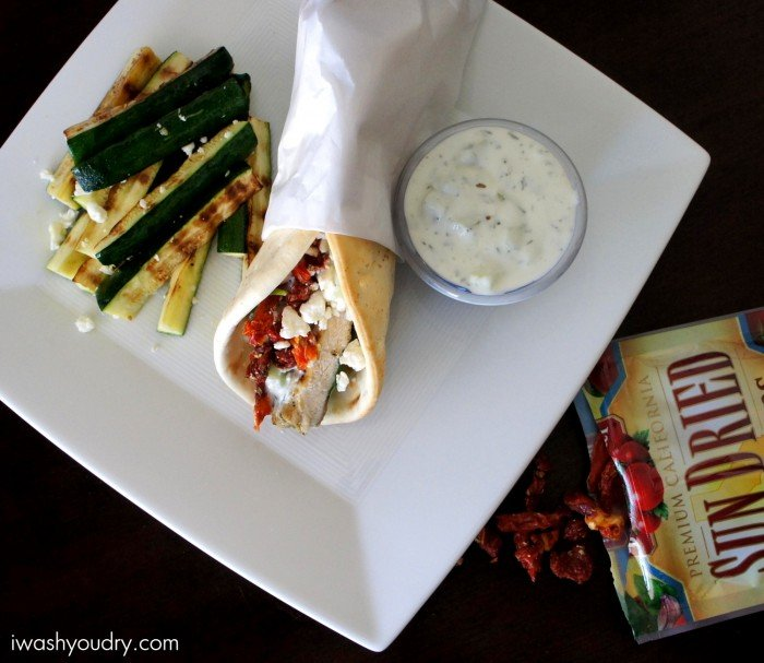 A wrapped Grilled Chicken Souvlaki Pita next to a small bowl of sauce and grilled zucchini sticks