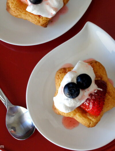 Strawberry Shortcake Cookies topped with whipped cream displayed on a plate.