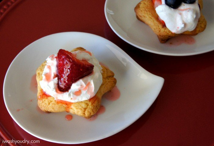 Strawberry Shortcake Cookies topped with whipped cream and a strawberry displayed on a plate