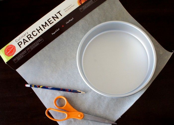 supplies on a table: parchment, a round cake pan, a pencil and scissors