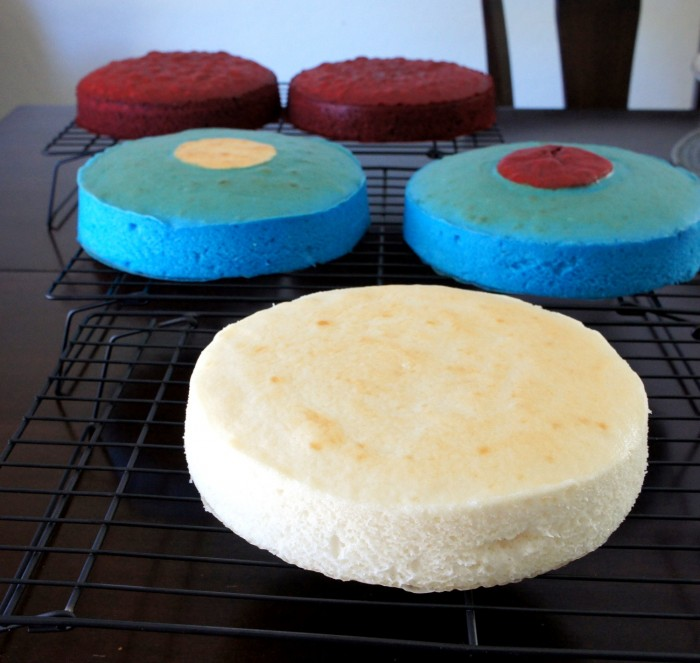 5 cake layers cooling on a cooling rack, 2 red layers, 2 blue layers with different colored centers and one white layer