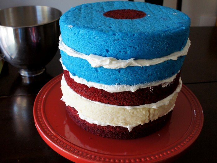 Five layers of cake stacked on top of each other with white icing between each layer. The layers are red, white, red, blue and blue