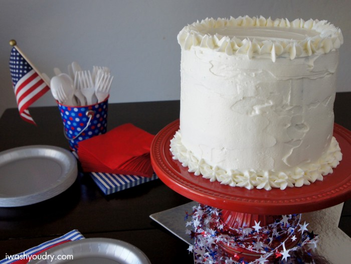 A white frosted cake sitting on top of a table with other patriotic decorations and napkins nearby