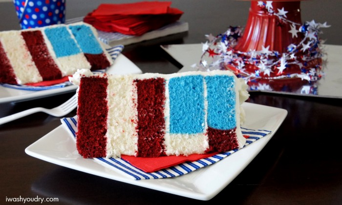 A piece of 5 layer cake sitting on top of napkins and a plate, with red, white and blue layers