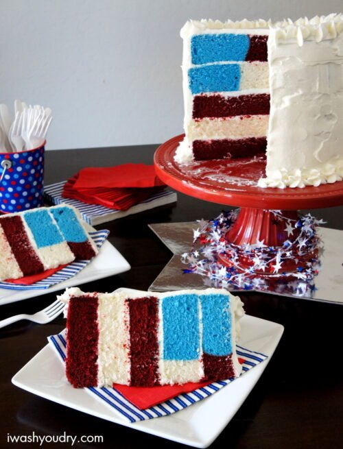 Slices of 5 layer 4th of July themed birthday cake on plates next to the full cake on a cake stand.