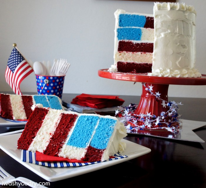 A red, white and blue cake sitting on top of a table with a slice taken out of it and slices of cake on the table in front of it