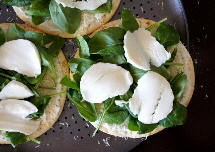 A close up of pitas on a pan with spinach and sliced cheese on top
