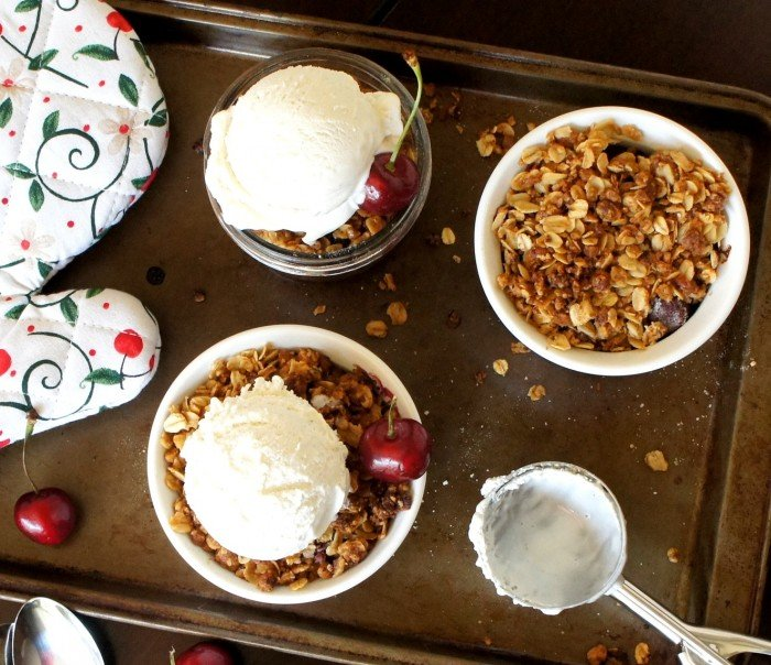 A look down on three bowls of Sweet Cherry Crisp, two with a scoop of vanilla ice cream and a cherry on top